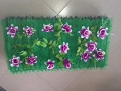 Rug from artificial greens and flowers